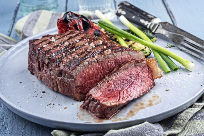 白色盘子上席伦牛排和刀叉