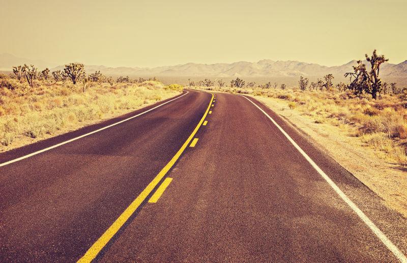 昏黄的天空下的复古电影风格美国无尽的乡村公路
