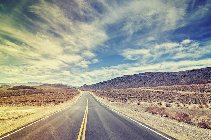 蓝天白云下 沙漠里的长长的乡村公路