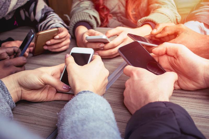 一群朋友使用移动电话坐在桌子旁
