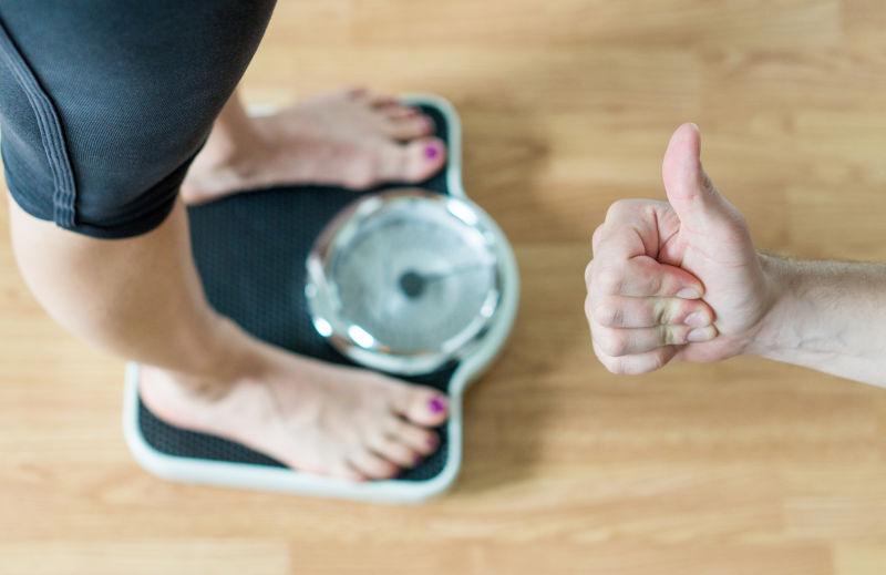 站在秤上减肥成功的人和人竖大拇指的人