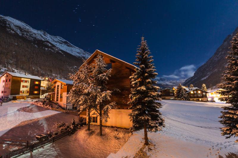 夜晚覆盖着雪的山峰背景下的冬季的小山村
