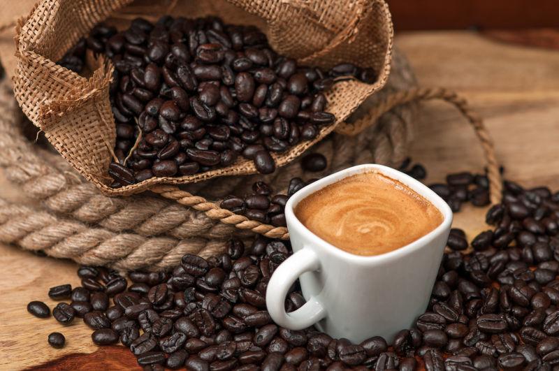 带子里的咖啡豆和装在杯子里的咖啡