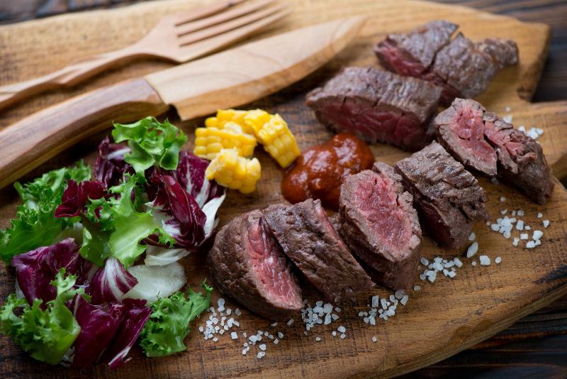 木盘上切好的烤牛排和木制刀叉