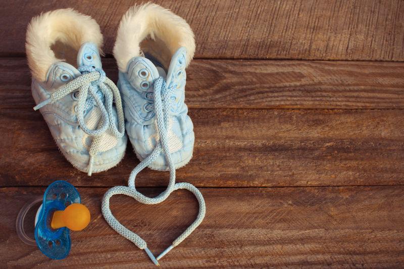 心的符号是画孩子的鞋带和39的鞋子和旧木板背景的奶嘴
