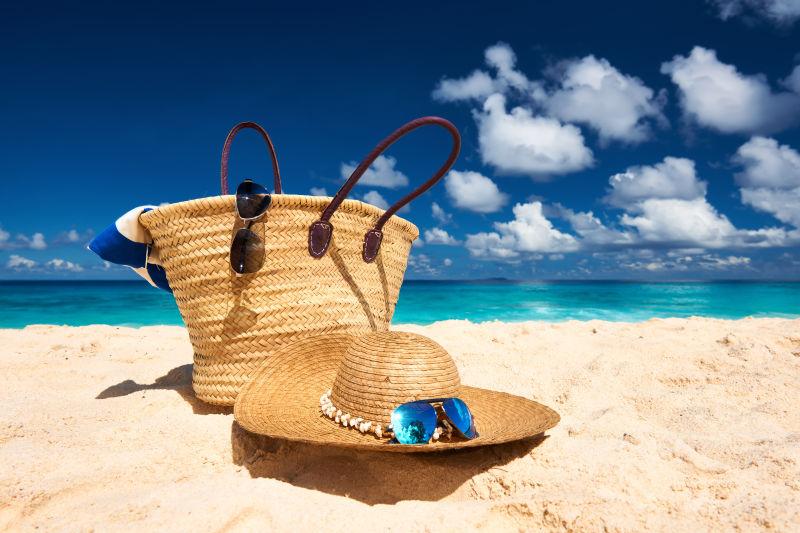 沙滩上的遮阳帽和旅游包