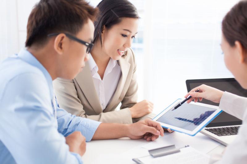 看着平板电脑讨论工作的三个商务人士