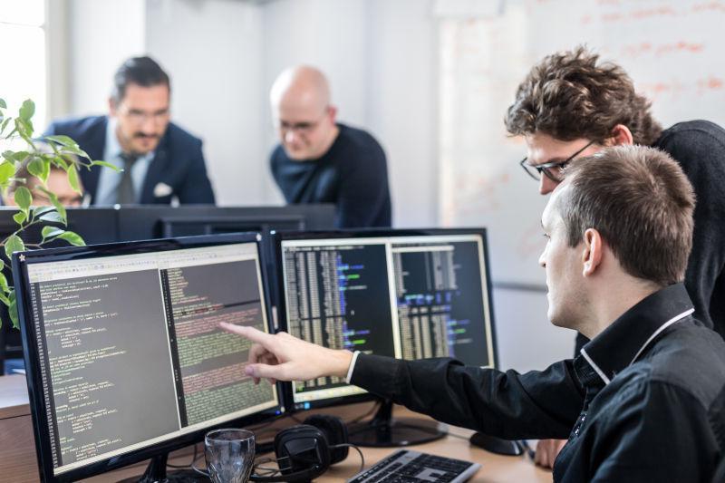 年轻的软件开发团队在启动公司共享办公空间的桌面计算机上进行头脑风暴和编程
