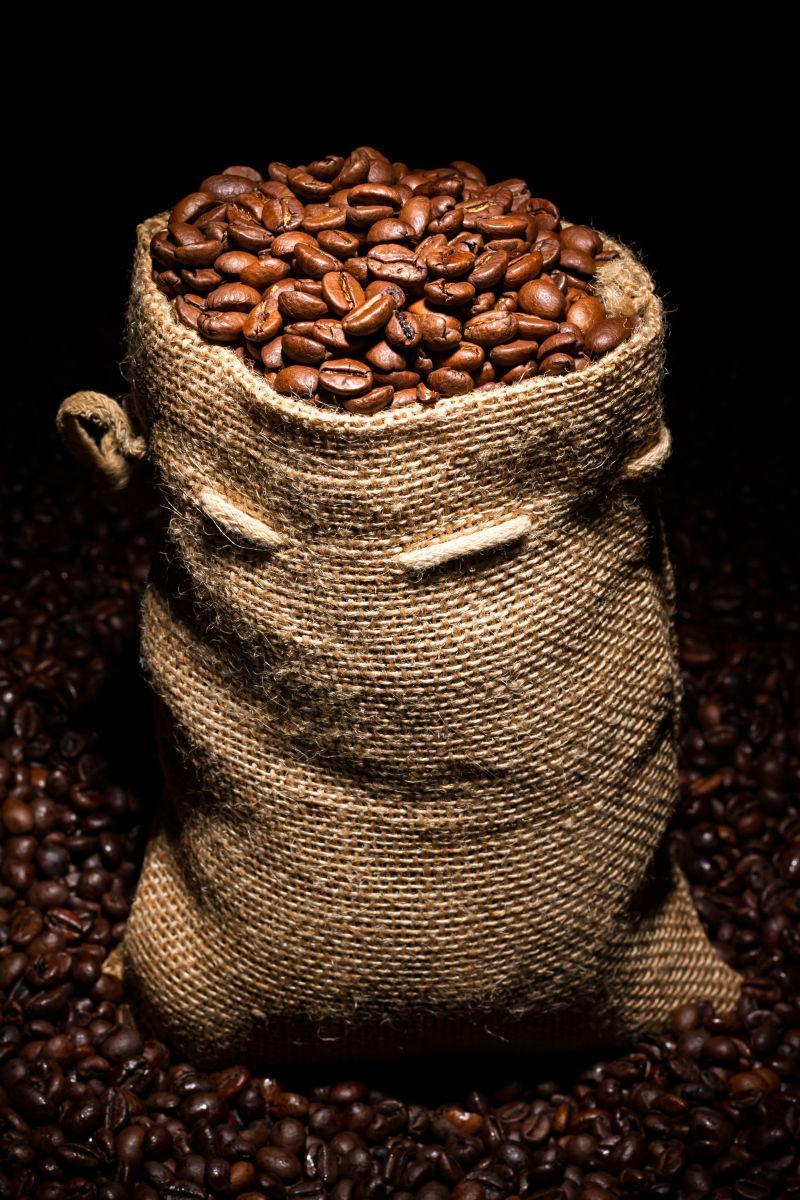黑色背景上装满咖啡豆的袋子