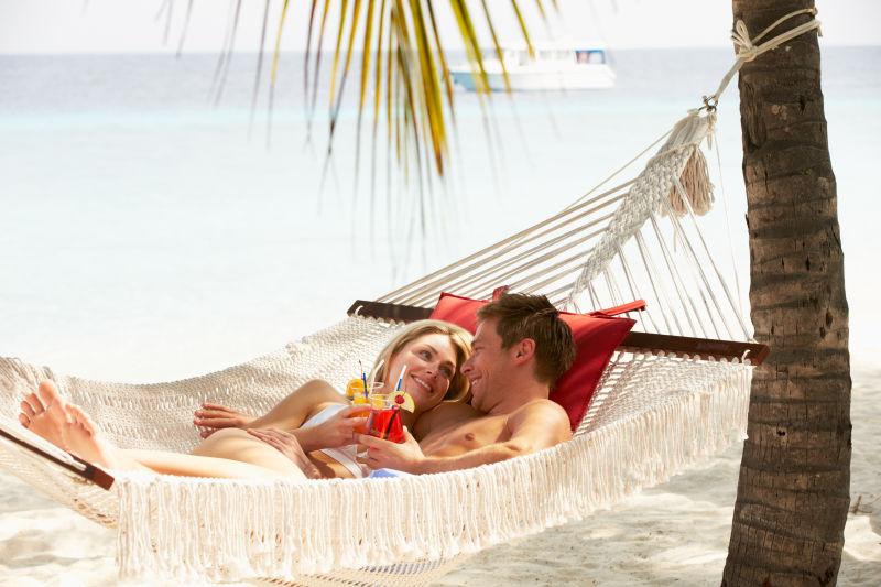 度蜜月的夫妇在海滩吊床上