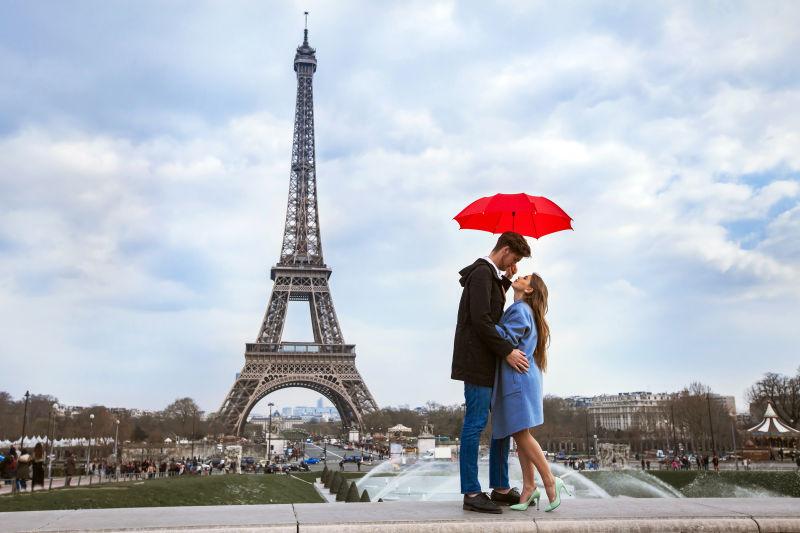 埃菲尔铁塔附近红色伞下的情侣