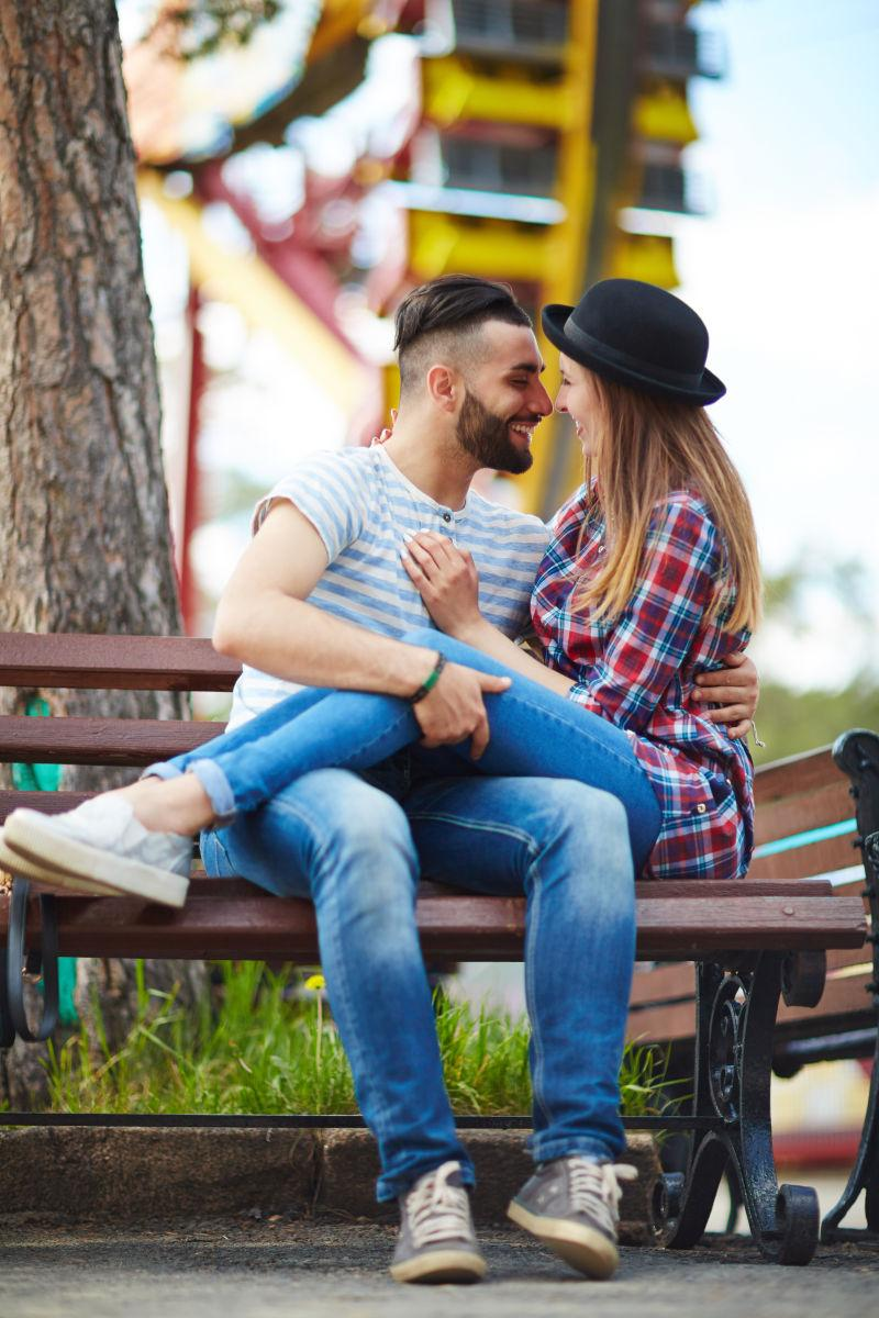 坐在公园长椅上的调情夫妻