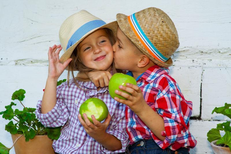 戴帽子的情侣儿童拿着苹果