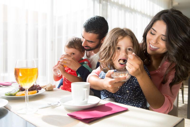 年轻的拉丁裔家庭和孩子们一起吃早餐