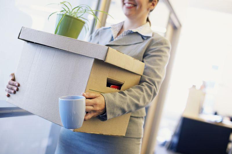 抱着纸箱拿着杯子的女人