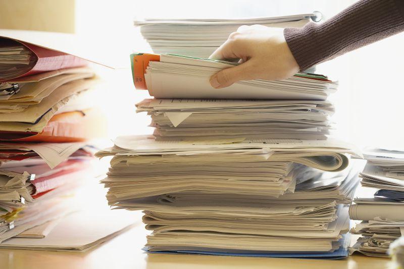 办公桌上一只手翻看堆积的档案文件