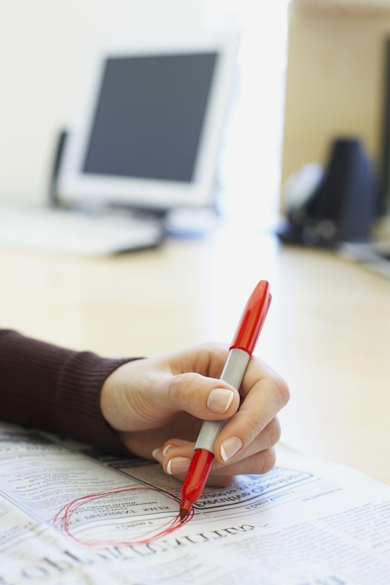 办公桌上用笔在报纸上画红圈的人