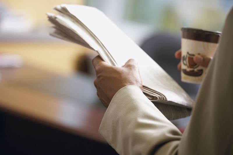 拿着报纸端着咖啡的男人