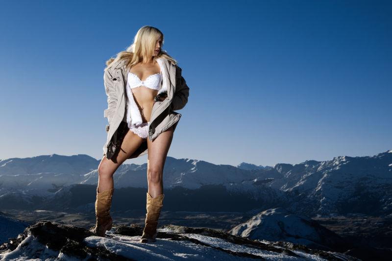 蓝天和群山背景下站立的穿着比基尼和大衣的美女