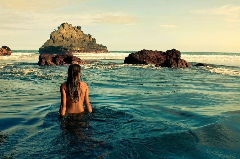 夕阳下水里光裸着后背的美女