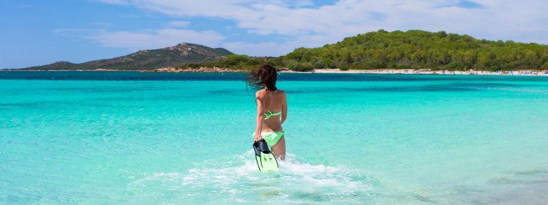 蓝天白云下穿着绿色比基尼手拿浮潜器走向海里的美女