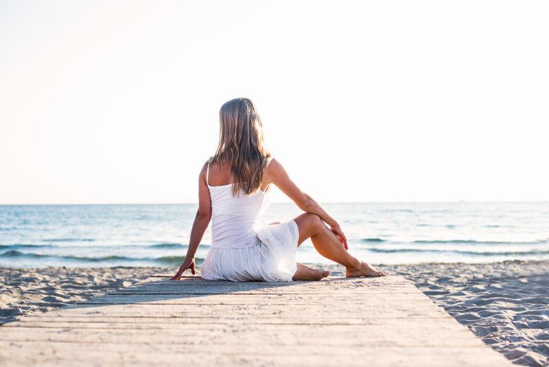 夕阳下坐在海边的穿着白色裙子的女人