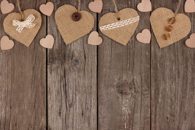 木制背景上手工编织的麻布爱心