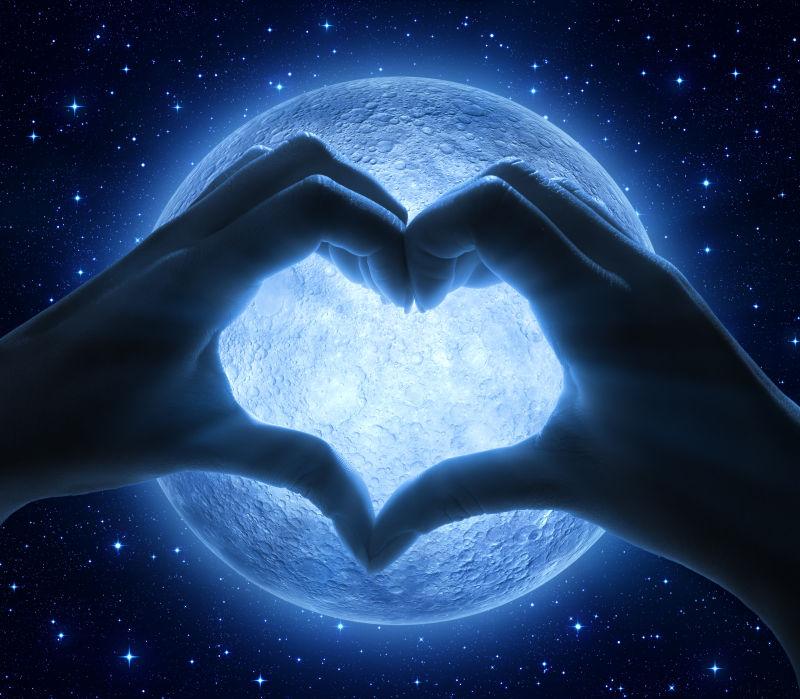 月亮背景前将手拼成爱心形状