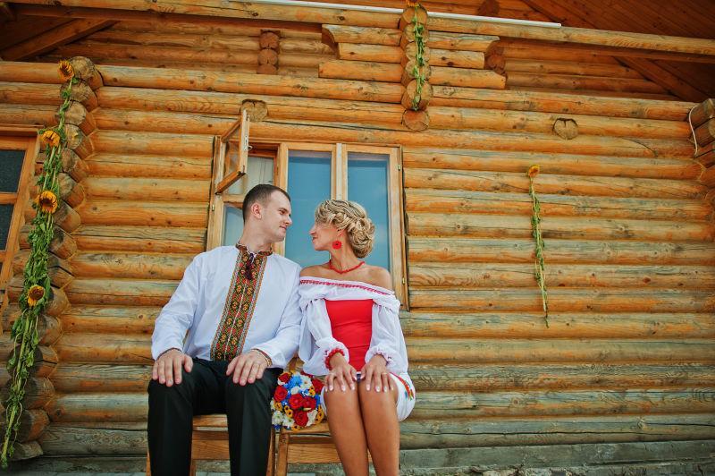 木屋外相互对视的新婚夫妇