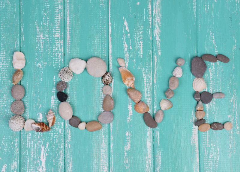 木制背景下贝壳和石头组成的英文爱