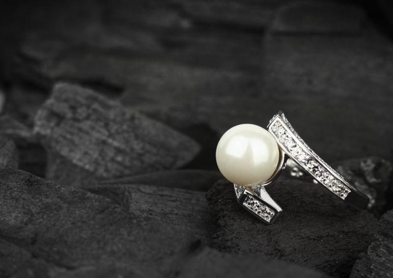 黑色煤炭背景上的珍珠钻石戒指