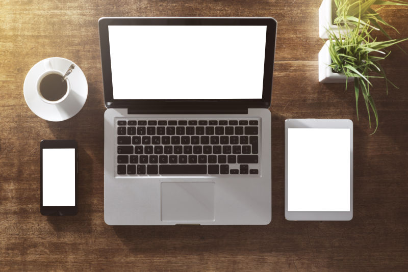 硬木桌上的空白屏幕的智能设备