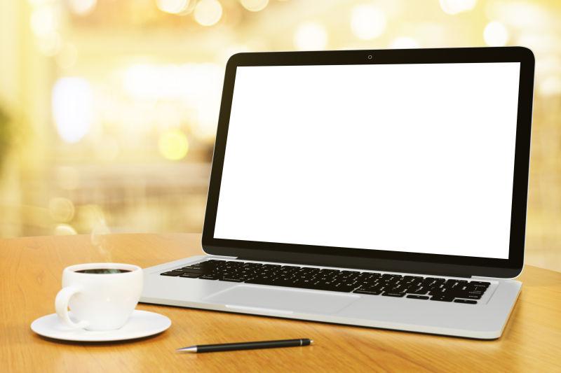 空白屏幕的笔记本电脑咖啡杯和笔