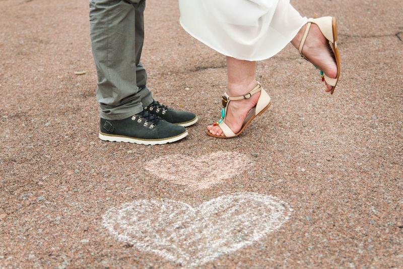 地面上的两个心形和年轻夫妇的脚