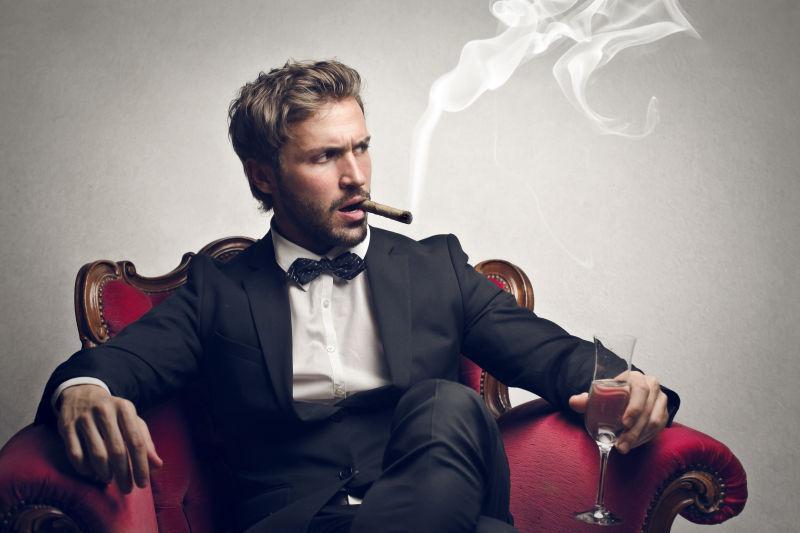 坐在红色沙发上男人抽着雪茄