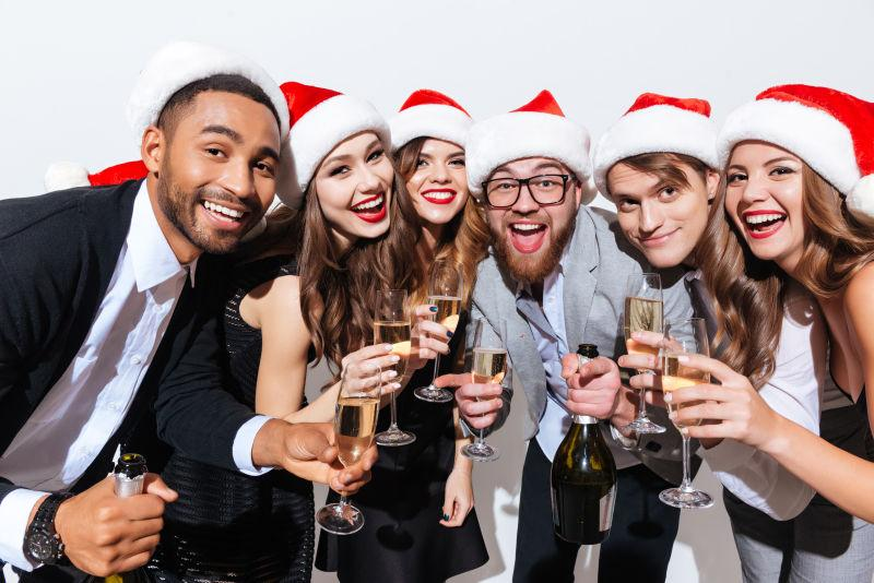 白色背景前戴着圣诞帽子的年轻人派对