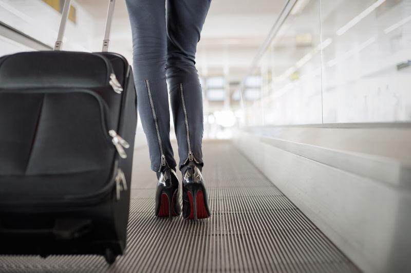 机场里带手提箱坐电梯的女人