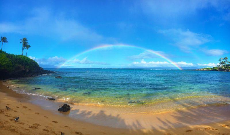 沙滩背景中的全景彩虹