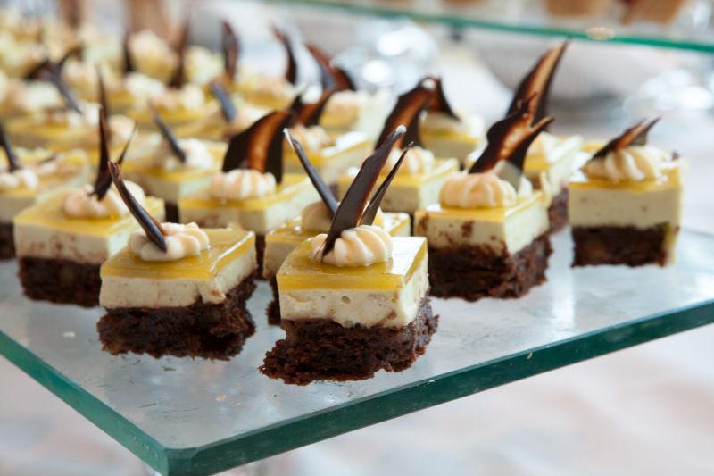 玻璃桌上的美味可口的黄色和巧克力小蛋糕