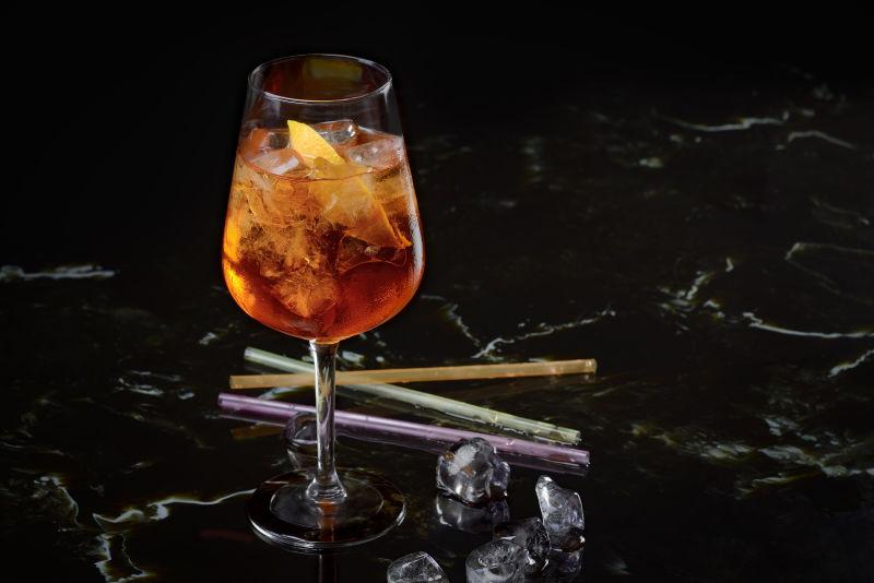 黑色背景上的鸡尾酒杯里的彩色水果鸡尾酒