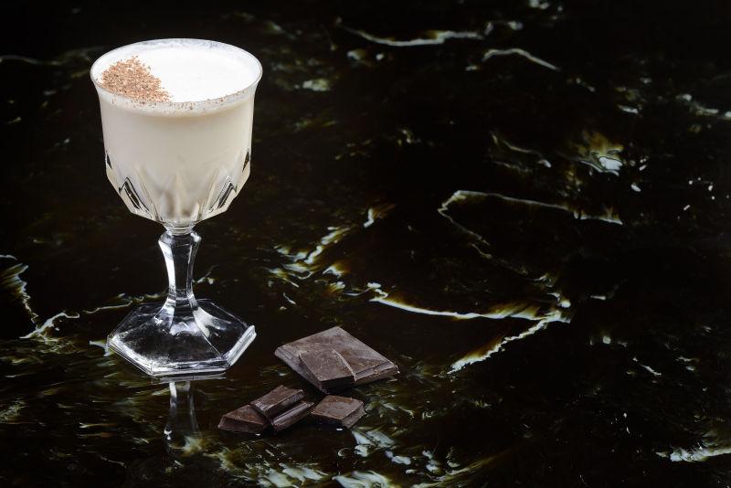 黑色背景上的鸡尾酒杯里的牛奶巧克力