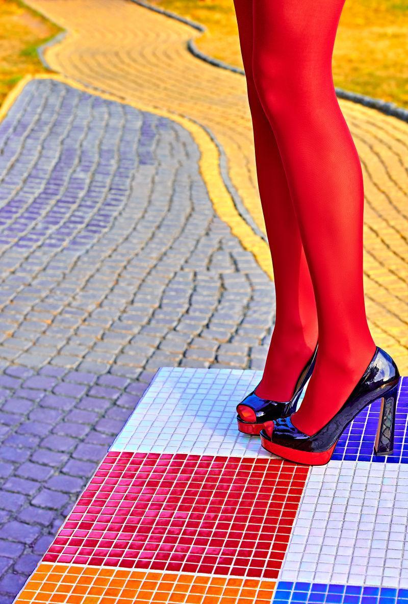 穿着红色连裤袜在马赛克路面上的女性时尚美腿