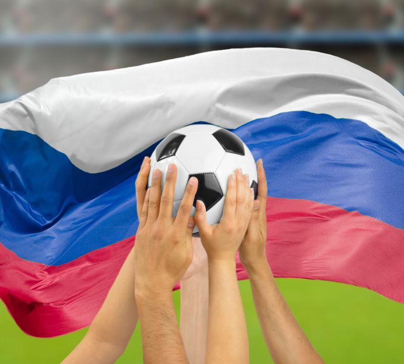 有国旗背景中很多手捧足球