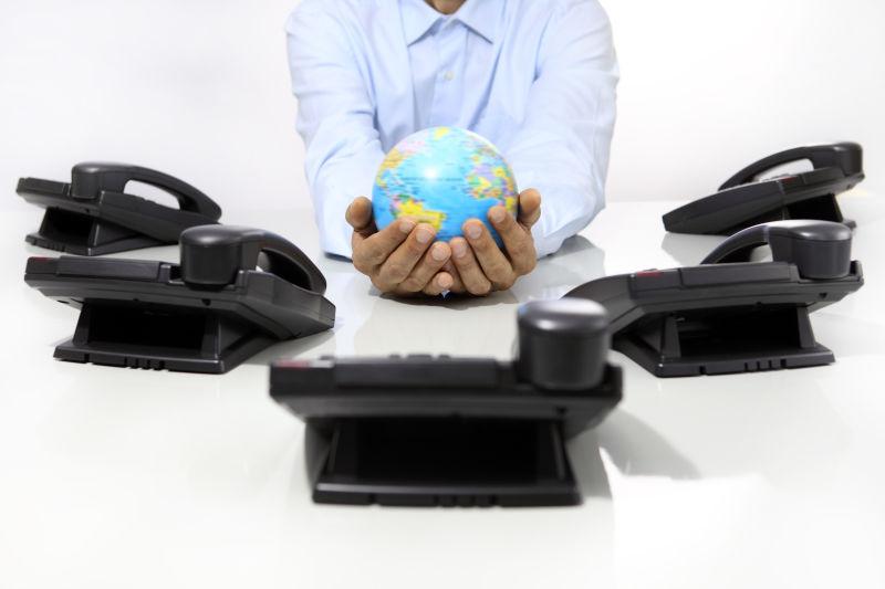 手拿地球仪和办公桌上的电话