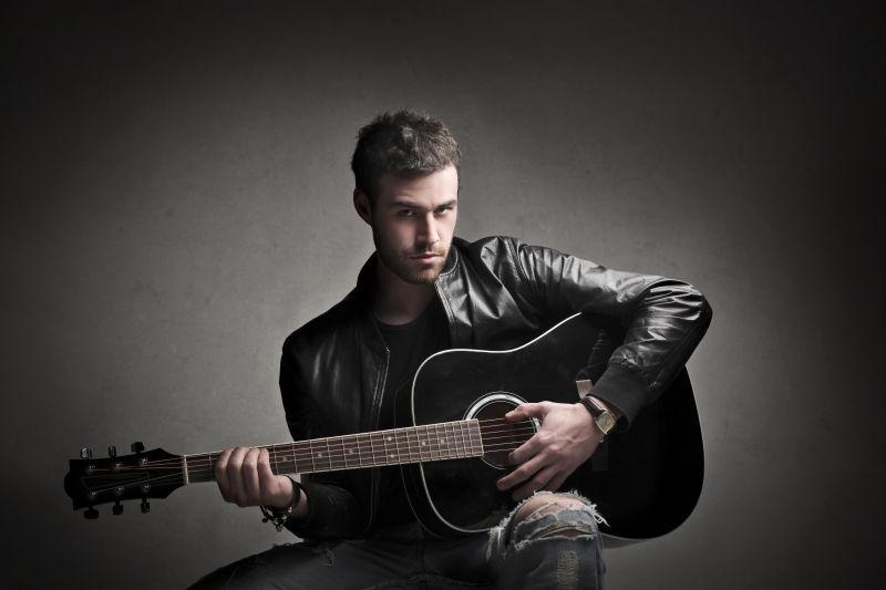 灰色背景中弹吉他的男人
