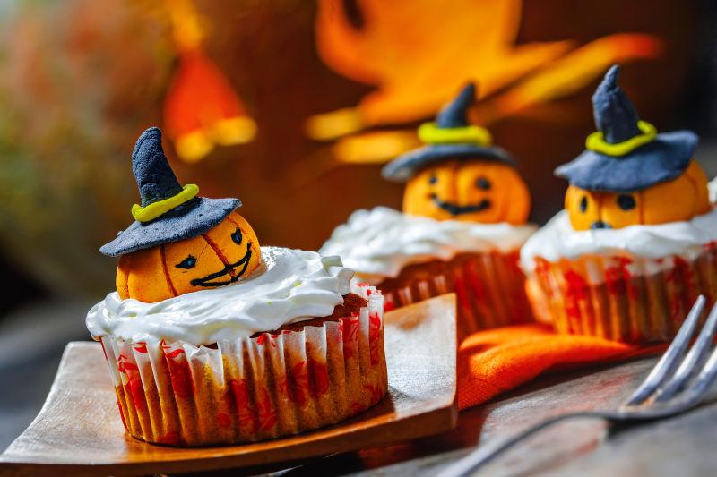 南瓜背景下的万圣节南瓜纸杯蛋糕