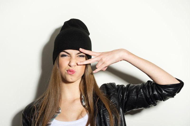 戴着黑色帽子的时髦的年轻女孩