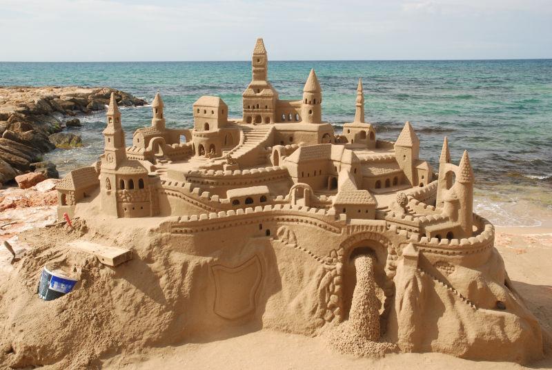 海边有阳光下的海滩上的沙滩城堡