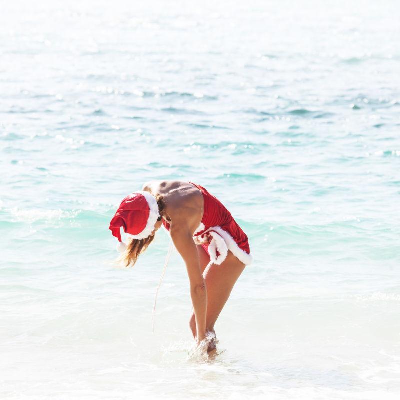 穿着圣诞老人衣服站在浅滩里的女士