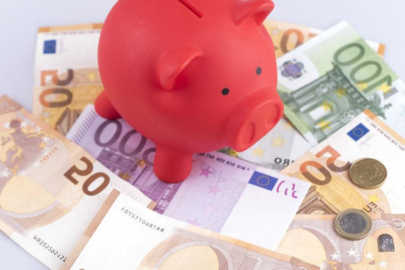 红色小猪存钱罐和货币